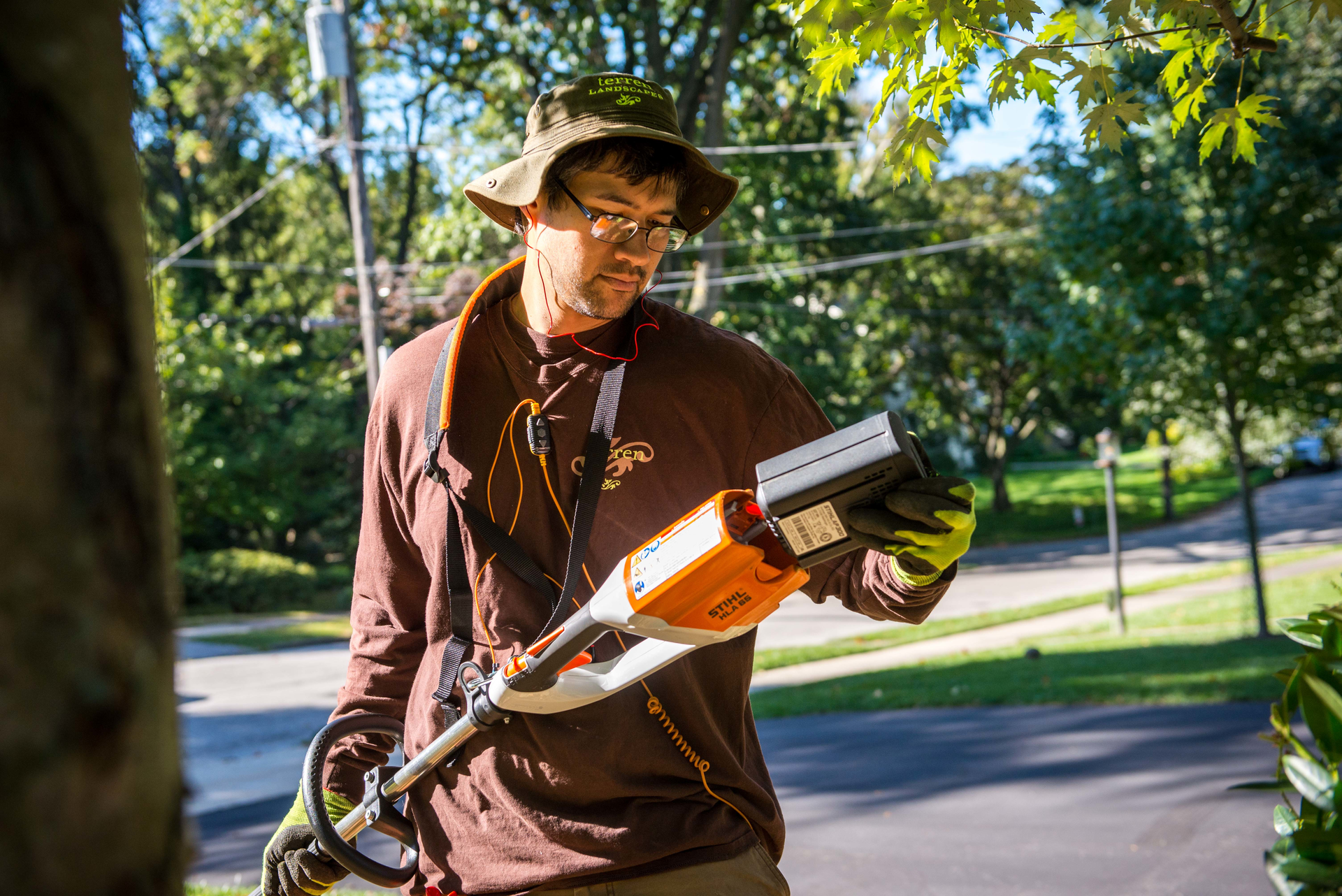 terren landscapes employee replacing the battery on a string trimmer